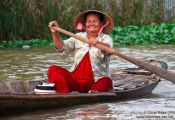Travel photography:Woman paddling her boat near Can Tho , Vietnam