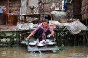 Travel photography:Washing the dishes in the Mekong near Can Tho , Vietnam