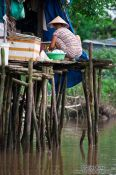 Travel photography:Woman on her stilt house near Can Tho , Vietnam