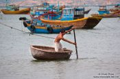 Travel photography:Man in a typical round boat in Mui Ne , Vietnam