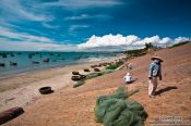 Travel photography:Women drying fish at the wharf at Mui Ne , Vietnam